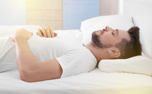Lie flat on your back. Use pillows to support your neck and bent knees.